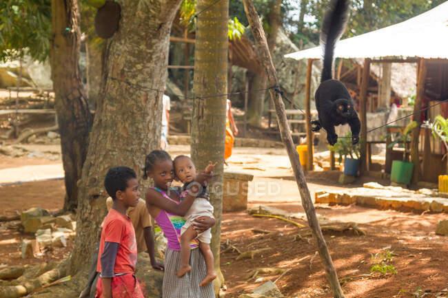 Madagascar, Antsiranana Province, Native children playing with a lemur — Stock Photo