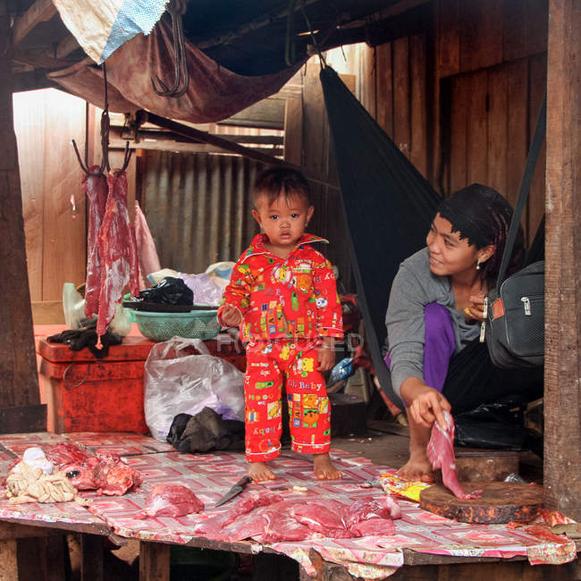 Mother with child in butcher shop, Cambodia — Stock Photo