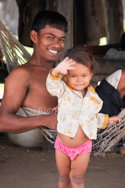 Чоловік з маленьким, за татом, дівчина махає перед камерою, сміючись дружньо, Камбоджа. — стокове фото