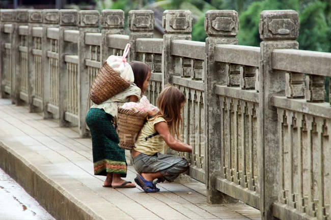 Laos, Two girls on the way home after buying or harvesting bananas and others, looking from the bridge to a river — Stock Photo
