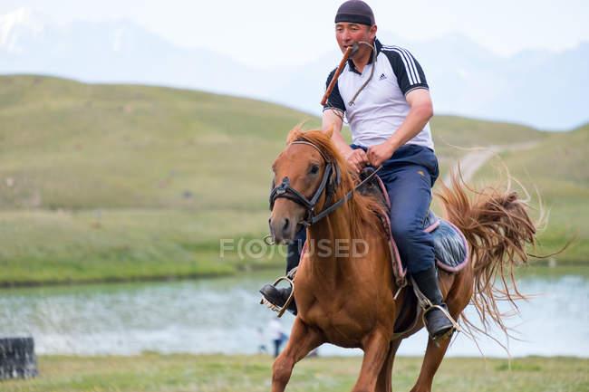 OSH REGION, KYRGYZSTAN - 22 июля 2017 года: Человек на лошади hore, горный пейзаж с озером на заднем плане — стоковое фото