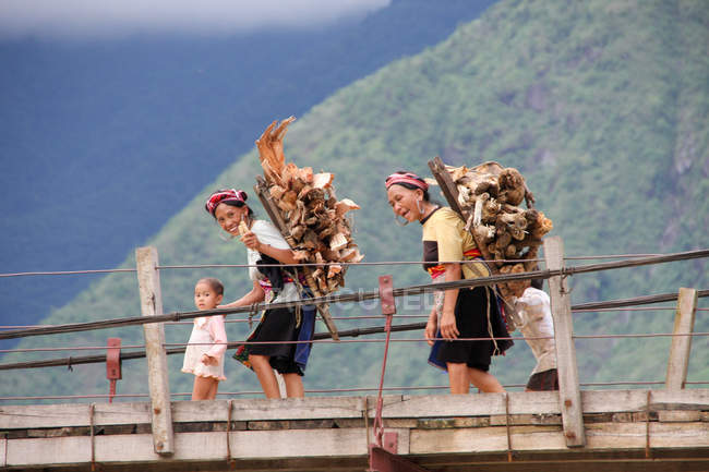Two women and little girls crossing bridge with chopped wood on back, Lao Cai, Vietnam — Stock Photo