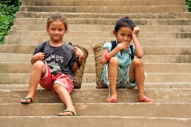 Laos, Dos chicas descansan en una escalera, cada una con cestas. - foto de stock