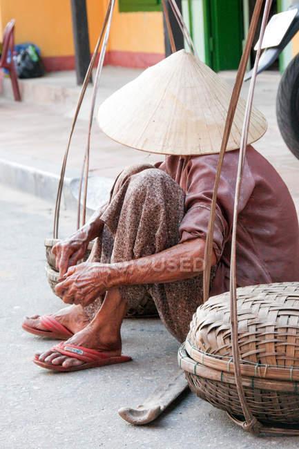 Vietnam, Vecchia signora seduta in strada e nascosta dietro un cappello conico — Foto stock