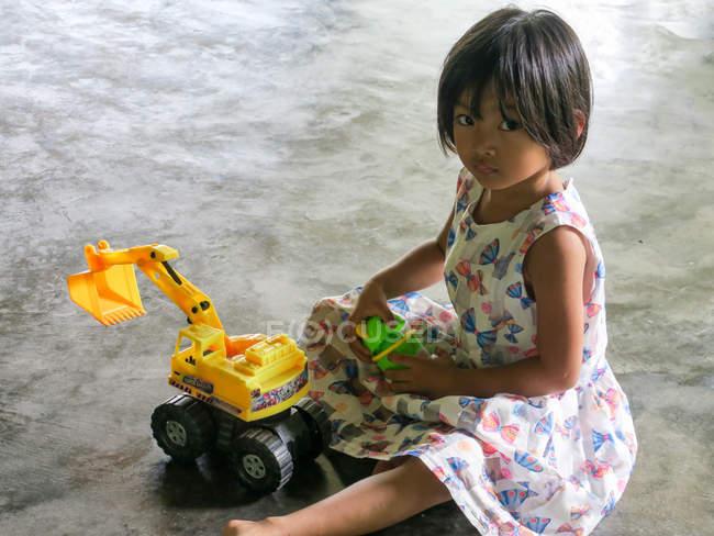 Дівчинка грає з іграшкою екскаватора на підлозі, Пханг Нга, Таїланд — стокове фото