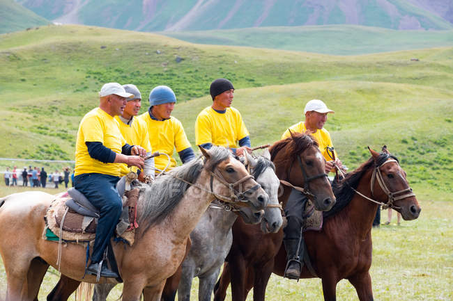 OSH REGION, KYRGYZSTAN - JULY 22, 2017: Nomadgames, goat polo, yellow team, men riding on horses — Stock Photo