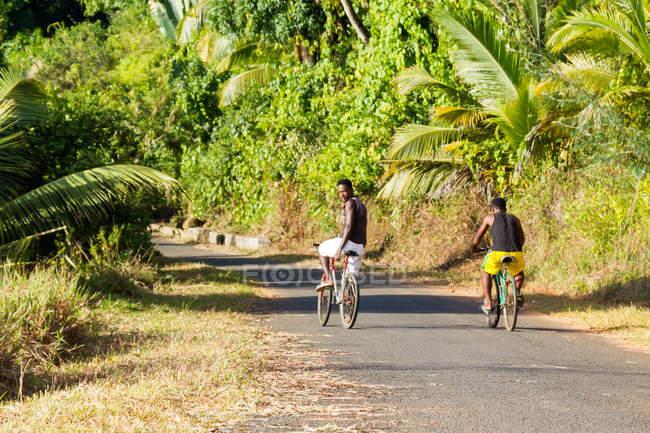 Zwei Männer Radfahren über Straße in Madagaskar, Afrika — Stockfoto
