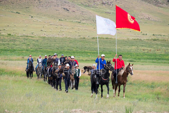 AK SAY, ISSYK-KUL REGION, KYRGYZSTAN - AUGUST 12, 2017: entry of athletes to the Nomad Games, local men riding horses — Stock Photo