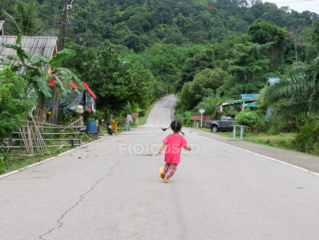 Girl running on empty road on street in Talaenok, Thailand — Stock Photo
