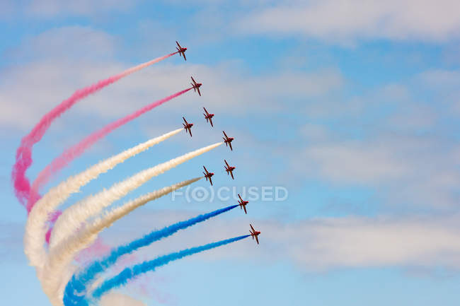 United Kingdom, Scotland, East Lothian, North Berwick, Red Arrows at the annual Scotlands National Airshow in East Fortune, performing aircrafts in sky leaving colorful contrails, bottom view — Stock Photo