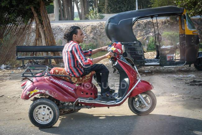 Seitenansicht der Mann auf dem Motorrad fährt vorbei Motor-Rikscha, Sakkara, Gouvernement Kairo, Ägypten — Stockfoto