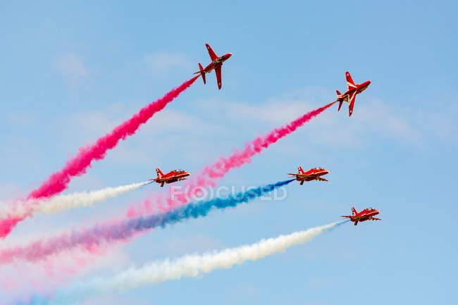 Reino Unido, Escócia, East Lothian, North Berwick, Red Arrows no show anual Scotlands National Airshow em East Fortune, realizando aeronaves no céu deixando contrails coloridos, vista de fundo — Fotografia de Stock