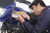 Mechanic working on motorcycle — Stock Photo