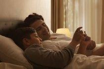 Padre e figlio che per mezzo del telefono intelligente — Foto stock
