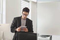 Uomo d'affari utilizzando la tavoletta digitale in ufficio — Foto stock