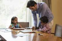 Father helping daughter and son — Stock Photo