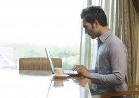 Homem no laptop no escritório em casa — Fotografia de Stock