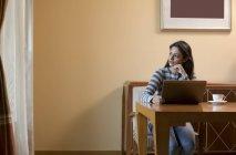 Mujer que trabaja desde su casa en un portátil - foto de stock