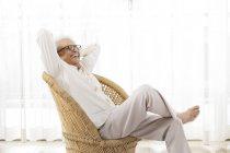 Усміхаючись старший людина сидить — стокове фото