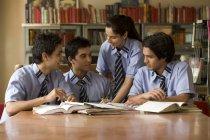 Estudiantes sentados en una biblioteca escolar - foto de stock