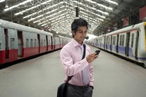 Businessman at a train station — Stock Photo