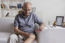 Homem aplicar a pomada no joelho — Fotografia de Stock