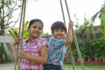 Brother and sister sitting on a swing — Stock Photo