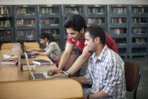 Étudiants avec ordinateur portable en bibliothèque — Photo de stock