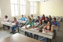 Estudiantes sentados en el aula - foto de stock