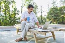Homme avec ordinateur portable et tasse de thé — Photo de stock