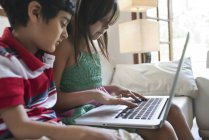 Brother and sister with laptop — Stock Photo