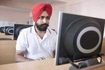 Man sitting in computer lab — Stock Photo
