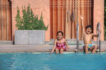 Kids sitting on edge of  pool — Stock Photo