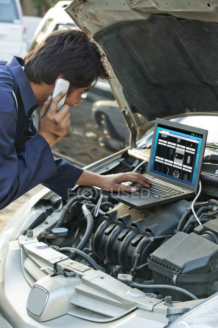 Mecânico falando enquanto usando laptop — Fotografia de Stock