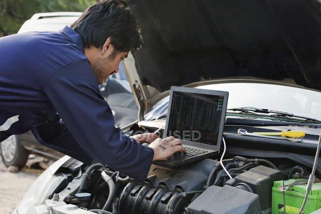 Mecânico usando laptop — Fotografia de Stock