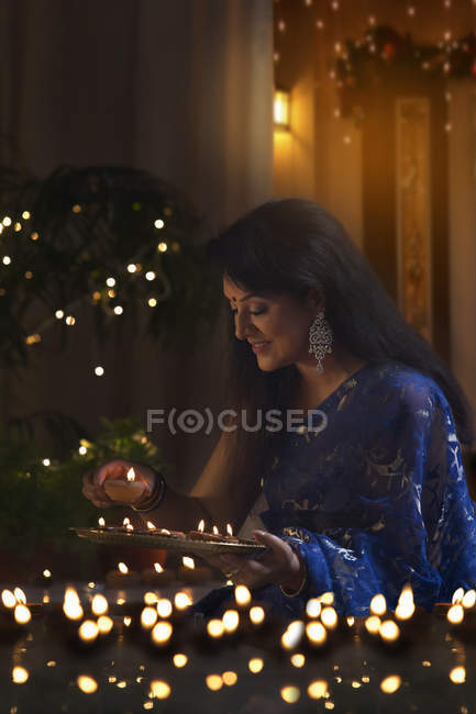 Woman in traditional sari arranging  lamps — Stock Photo