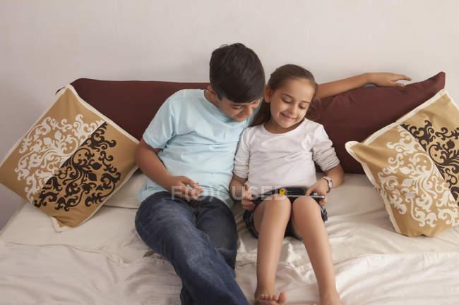 Irmão e irmã usando tablet digital — Fotografia de Stock