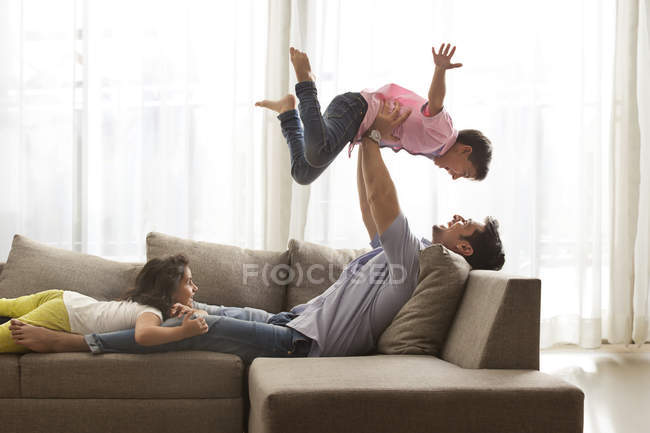 Father and children playing on sofa — Stock Photo