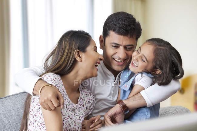 Playful family sitting on sofa — Stock Photo