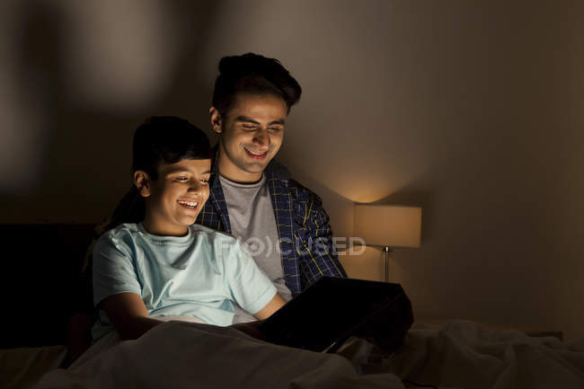Pai e filho usando tablet digital — Fotografia de Stock