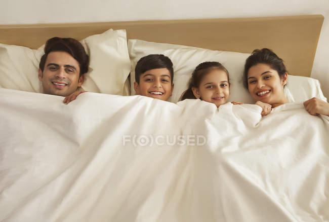 Família deitada na cama — Fotografia de Stock