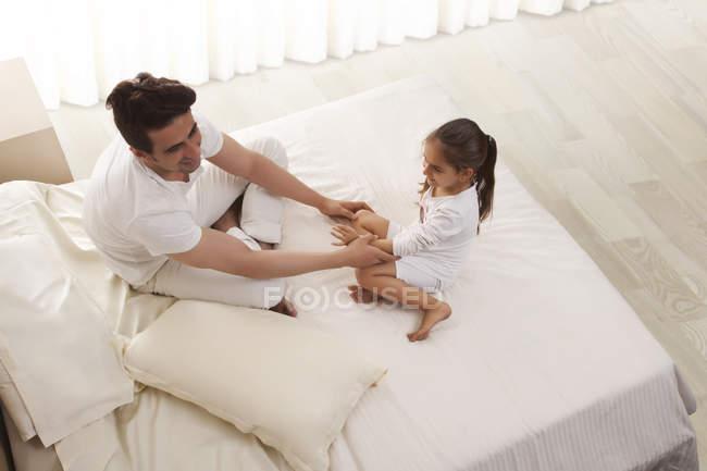Pai e filha sentada na cama — Fotografia de Stock
