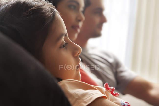 Девушка с родителями смотреть телевизор — стоковое фото
