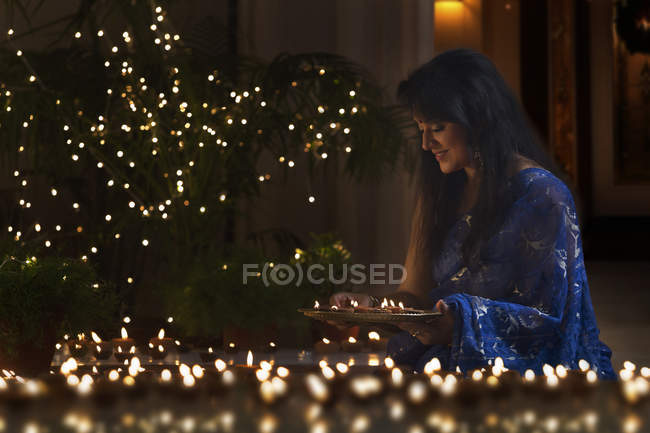 Woman arranging oil lamps — Stock Photo