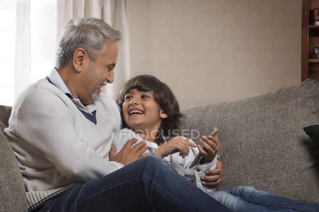 Дед и внук, с помощью мобильного телефона — стоковое фото