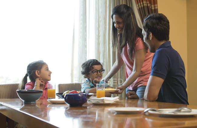 Mãe, servindo comida para a família — Fotografia de Stock