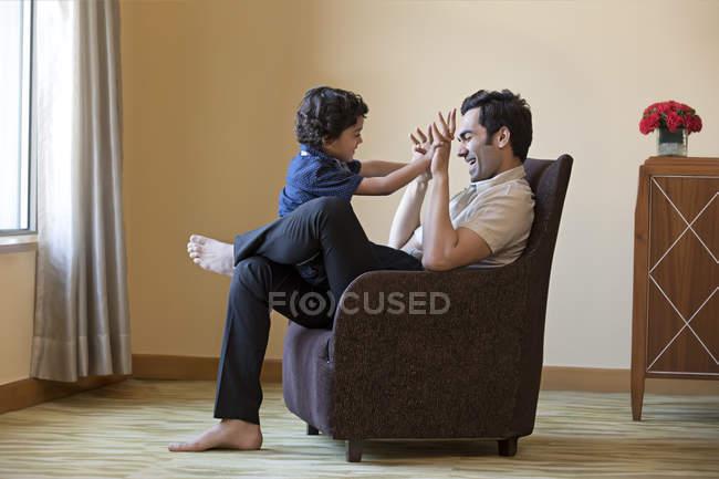 Jovem, brincando com seu filho — Fotografia de Stock