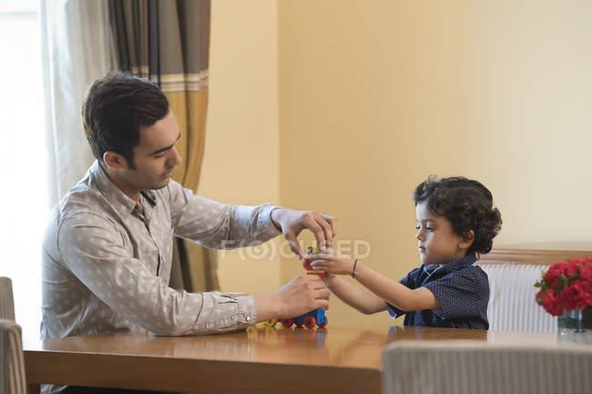 Отец помогает молодой сын играть — стоковое фото