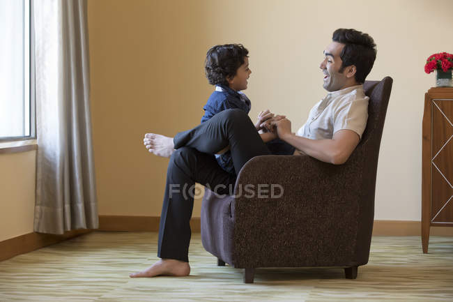 Отец и сын, сидя вместе — стоковое фото