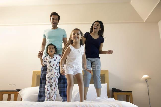 Família em pé na cama e jogando — Fotografia de Stock